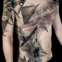 Татуировка в стиле треш-полька на груди и животе