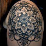 фотография черно-белой татуировки мандала лотос на плече